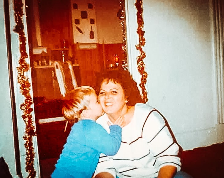 Old photo of son kissing mother, color photo