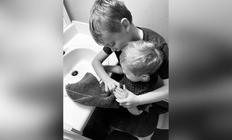 Big brother helping little brother wash hands, black-and-white photo