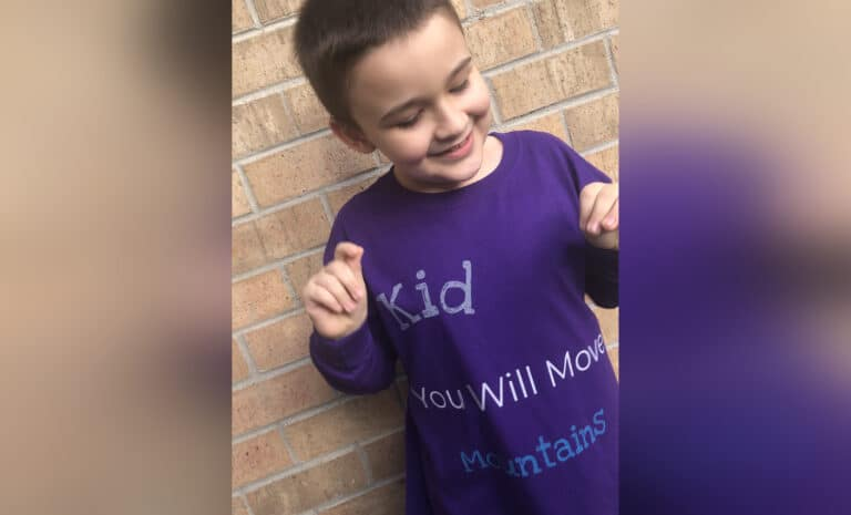 Little boy wearing you will move mountains shirt, color photo
