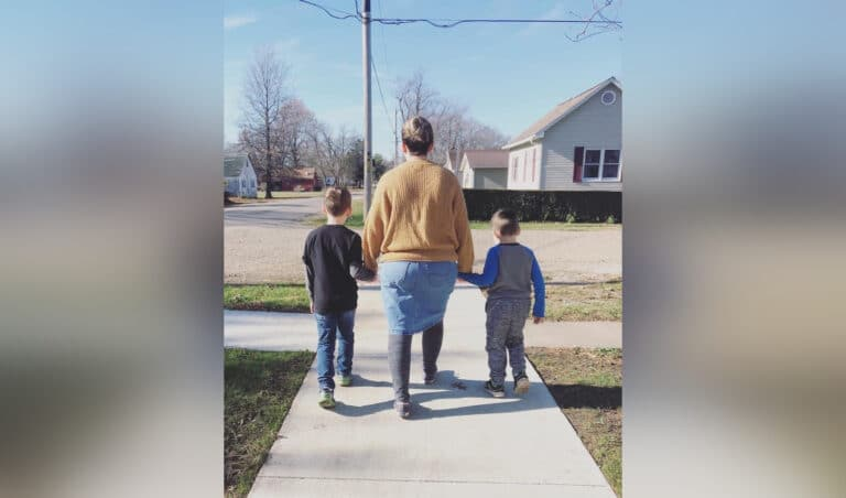 Mother walking down sidewalk with kids, color photo
