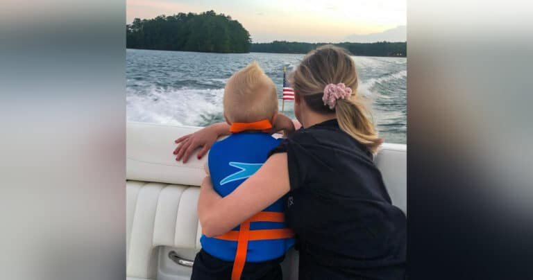 Woman holding child on boat, color photo
