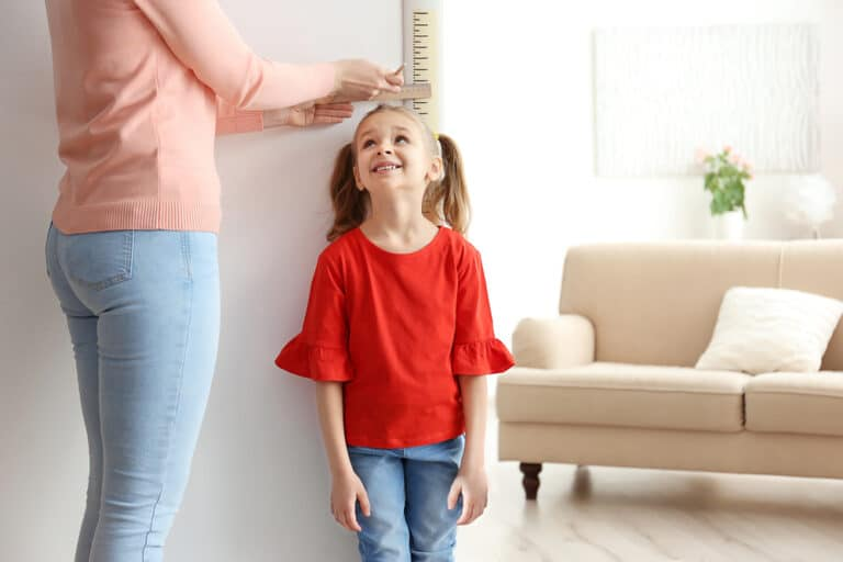 Mom measuring child on wall