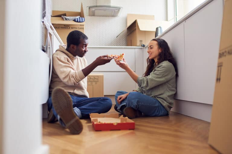 Couple eating pizza on kitchen floor