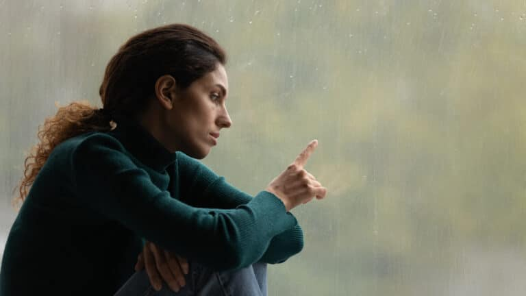Woman looking out window sadly
