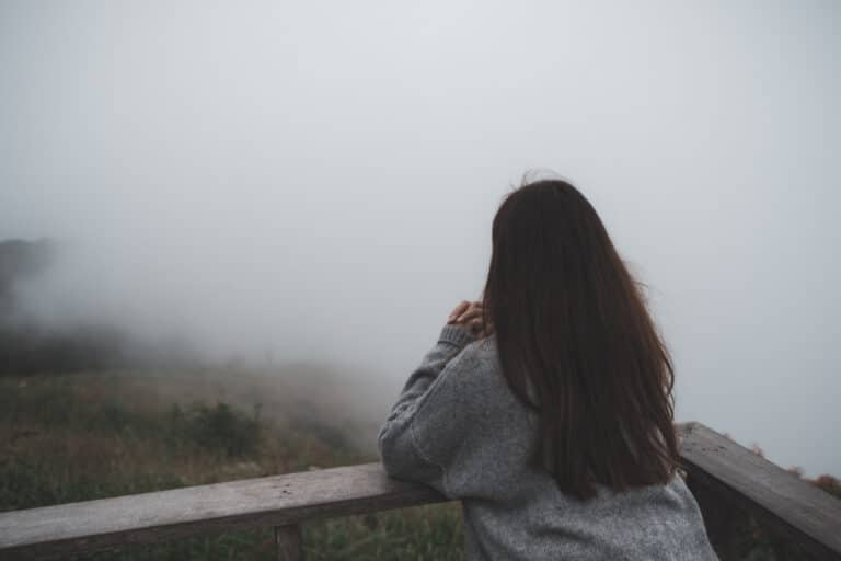 Sad woman looking into fog