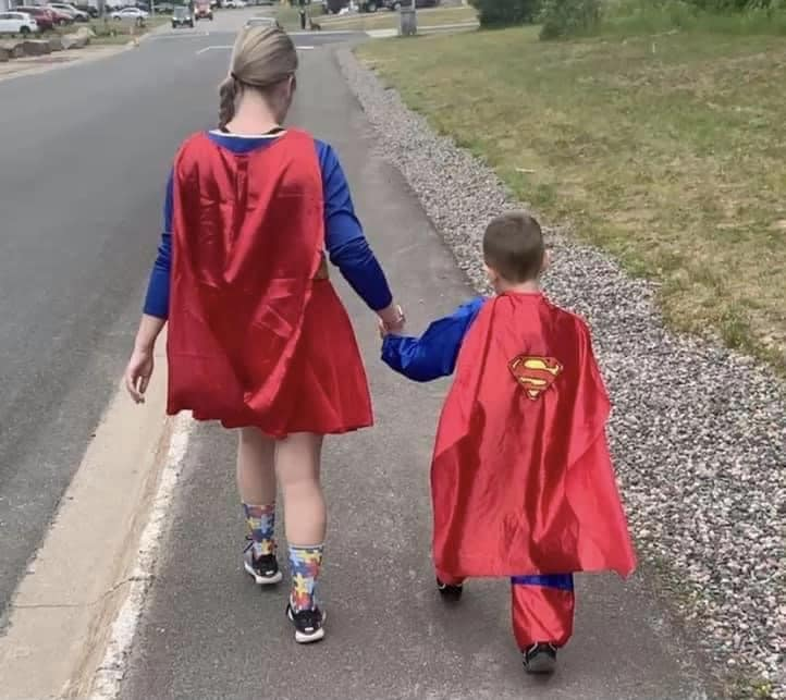 Mom walking with son in superhero capes