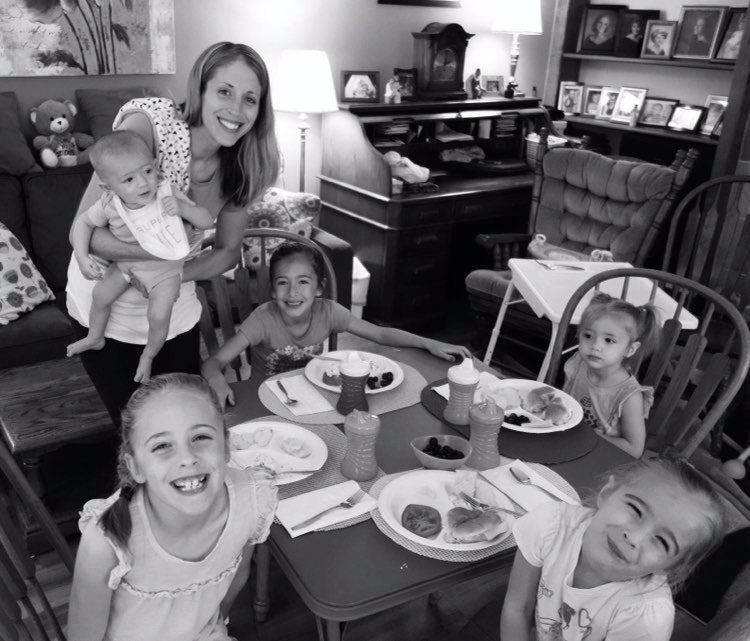 Woman holding baby at kitchen table with four little girls seated, black-and-white photo