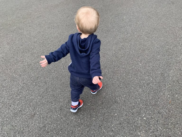 Toddler walking down sidewalk, color photo