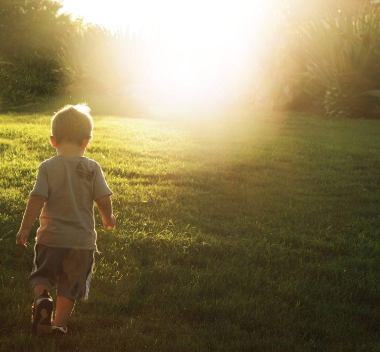 Little boy walking in grass, color photo