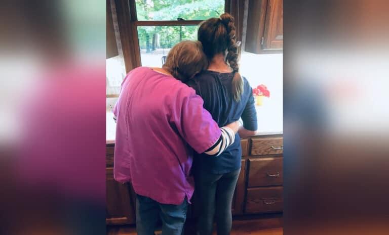 Mom hugging grown daughter at kitchen sink
