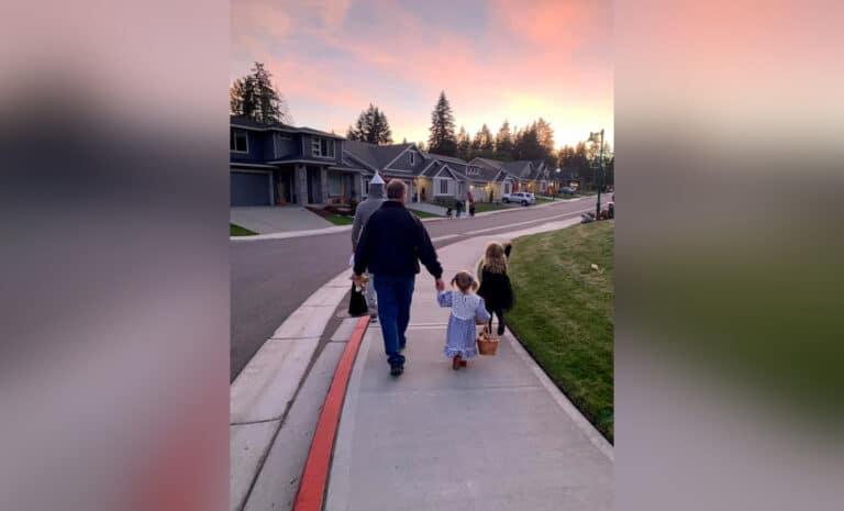 Man holding child's hand walking down sidewalk, color photo