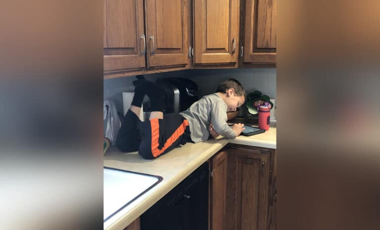 Boy sitting on counter with iPad, color photo
