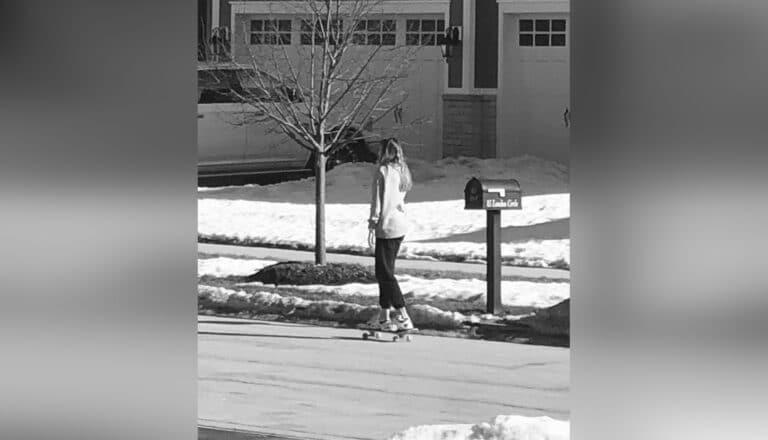Teen girl skateboarding, black-and-white photo