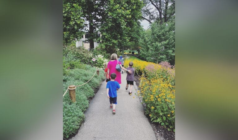 Mother walking with kids down sidewalk lined with flowers, color photo