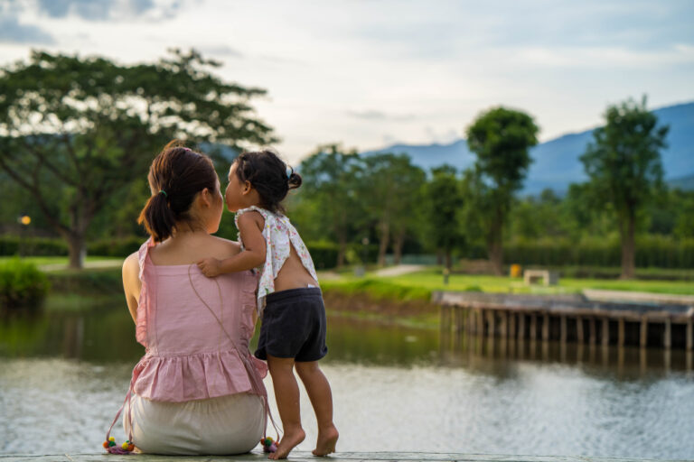 mom and daughter outside by water