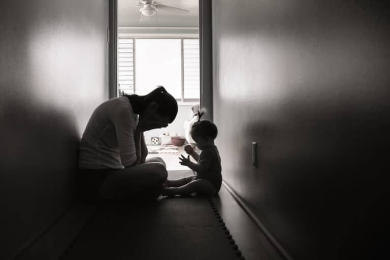 Sad mom in hallway with child