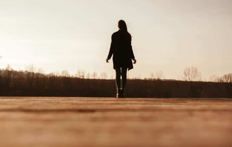 Woman walking down road alone