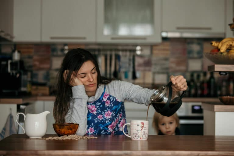Tired mother pouring coffee