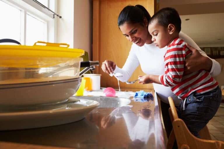 Mother doing dishes with toddler
