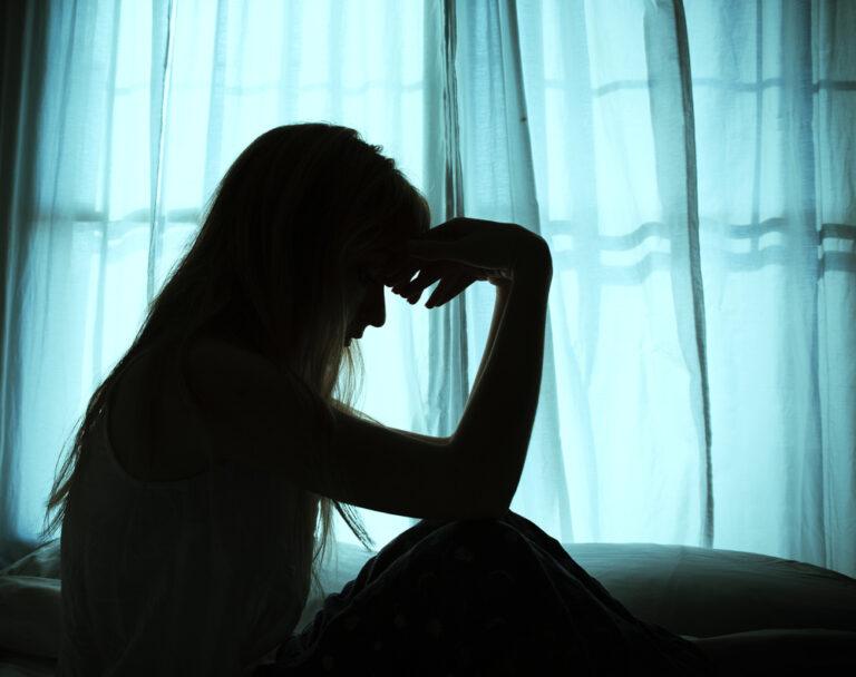 Sad woman sitting by window