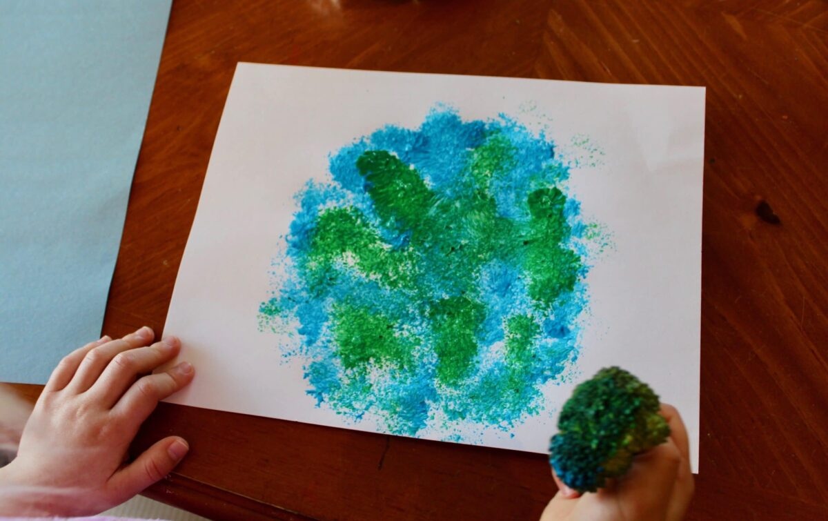 Child using broccoli to stamp art, color photo