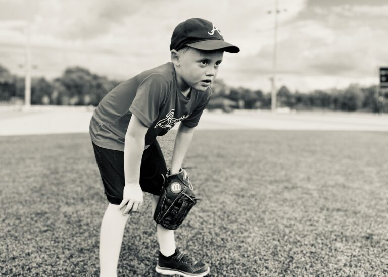 Boy standing with glove on knee on baseball field, black-and-white photo