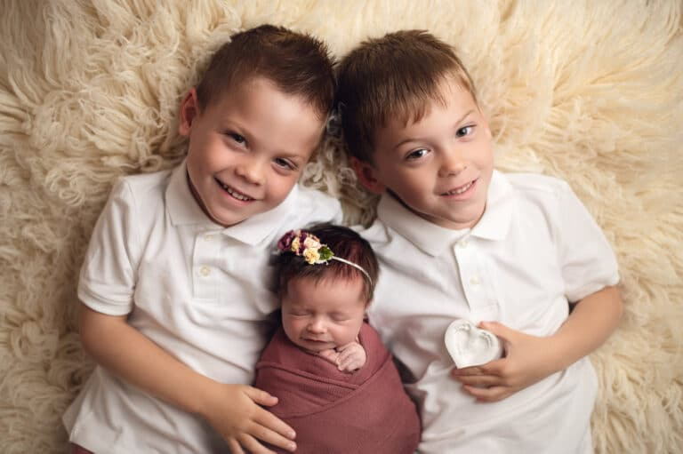 Two boys next to infant sister, color photo