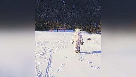 Child walking in snow, color photo