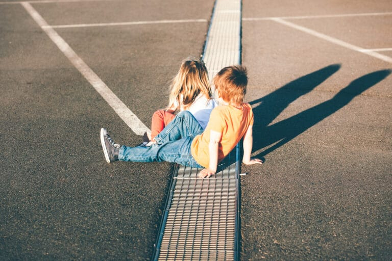 Two kids sitting on street