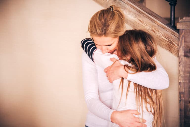 Mother hugging teen girl
