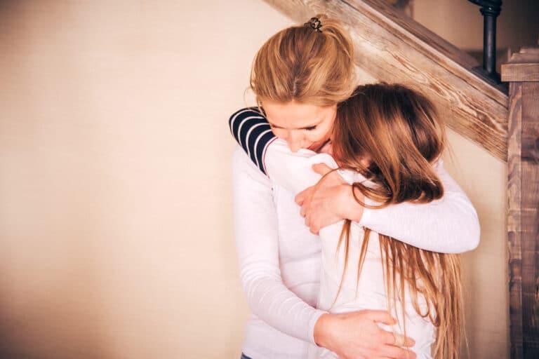 Mother hugging teen girl