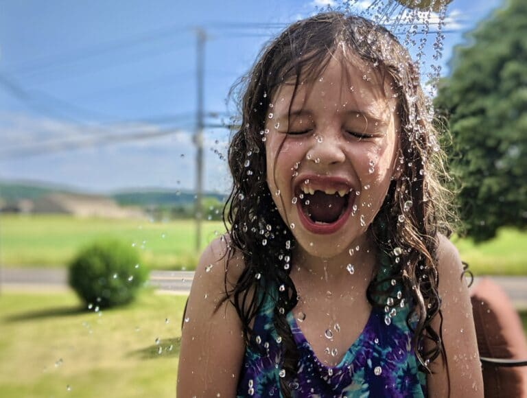 Child laughing in sprinkler