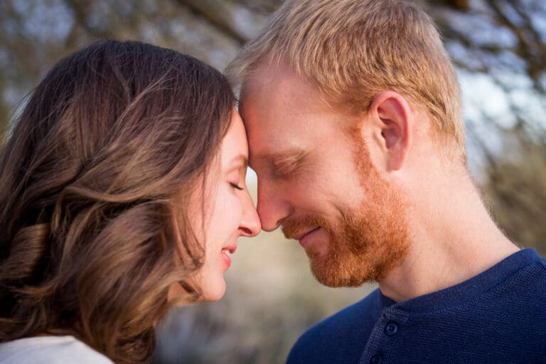 Husband and wife touching foreheads, color photo