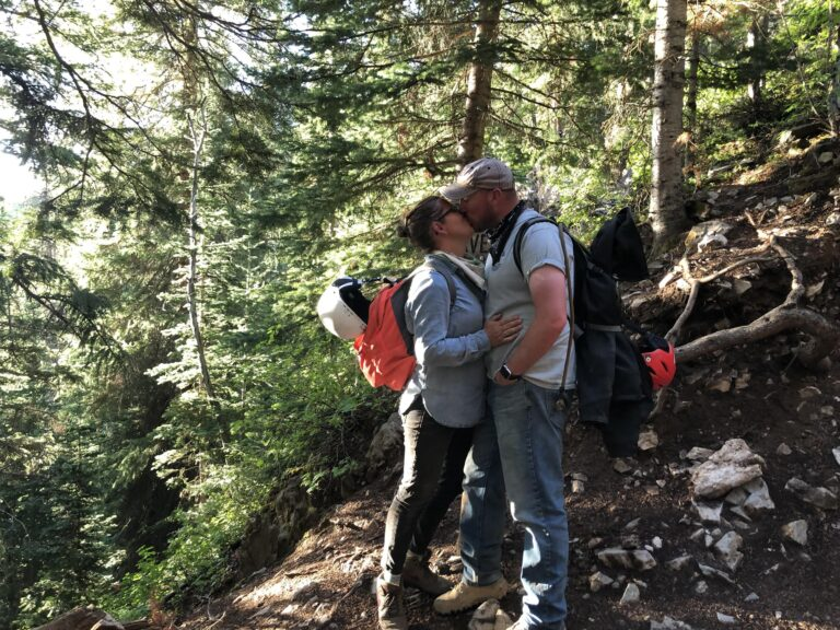 Husband and wife kissing in forest, color photo
