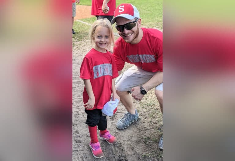 Little girl in t-ball uniform with dad, color photo