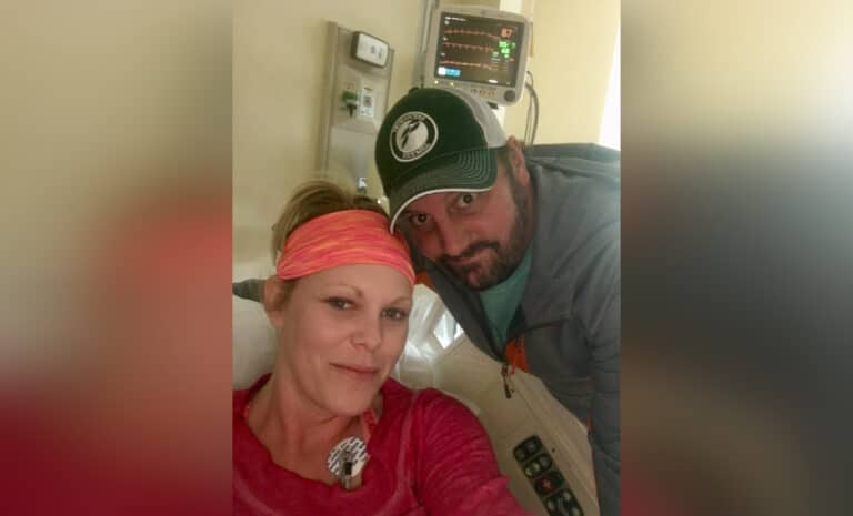 Wife sitting in hospital bed with husband beside her, color photo