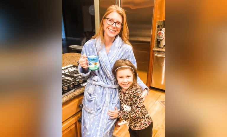 Woman in robe with coffee standing next to daughter, color photo