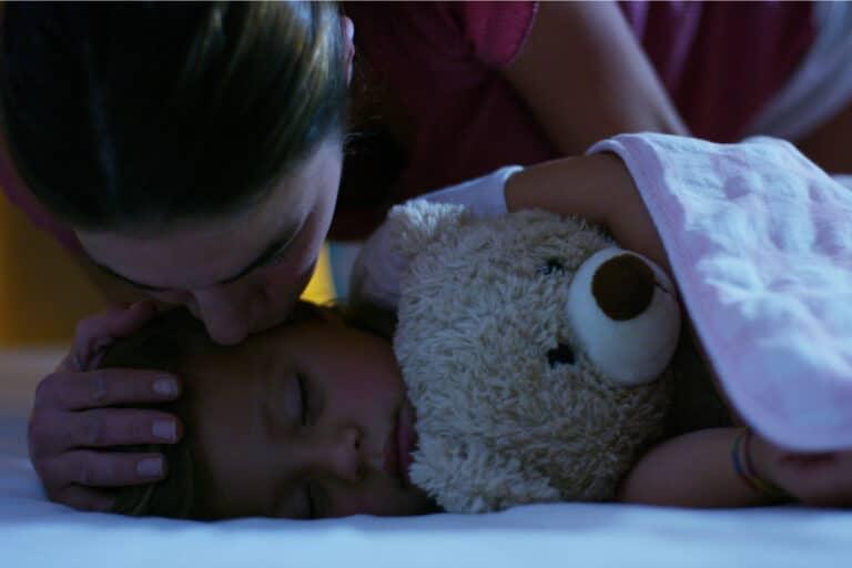 Mother kissing toddler at night