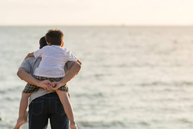 Father carries son on his back at the beach
