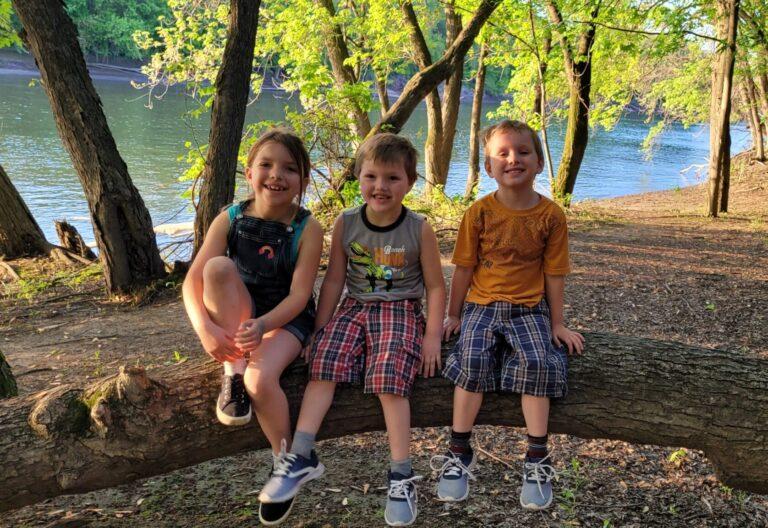 Three kids outside smiling