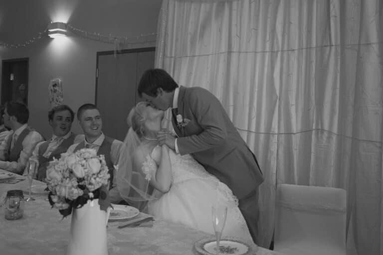 Groom kissing bride, black-and-white photo