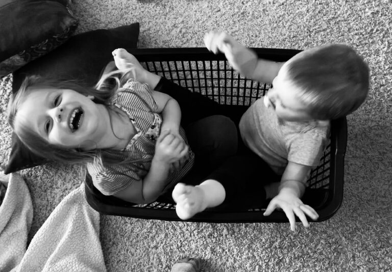 Two children in laundry basket, black-and-white photo