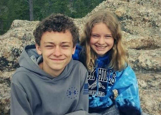 Tween boy and girl smiling, color photo