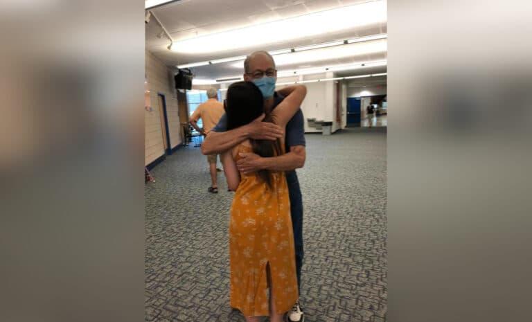 Grandpa hugging teen girl