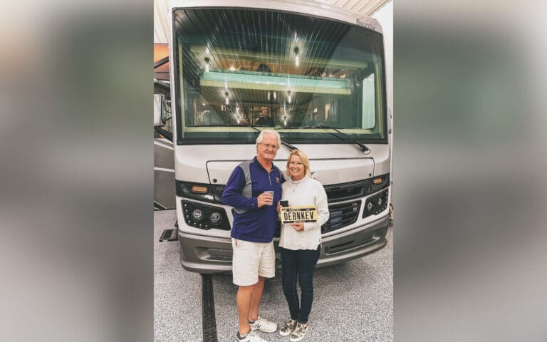 Husband and wife standing in front of RV, color photo