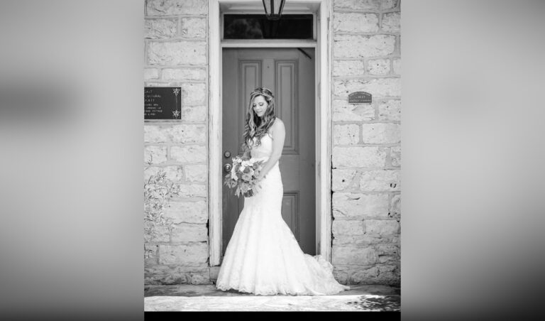 Bride holding bouquet, black-and-white photo