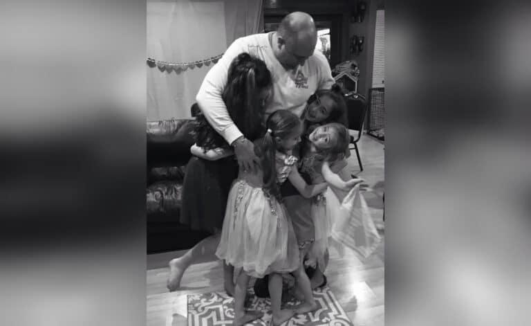 Dad hugging daughters