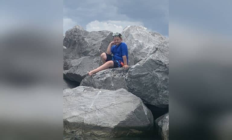 Young boy on rocks by ocean