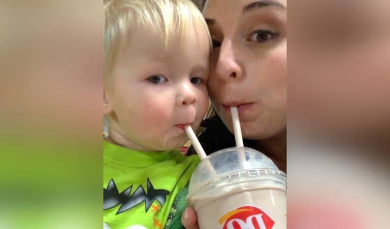 Mother sharing milkshake with child, color photo