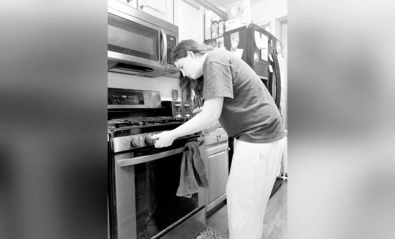 Woman standing at stove, black-and-white photo
